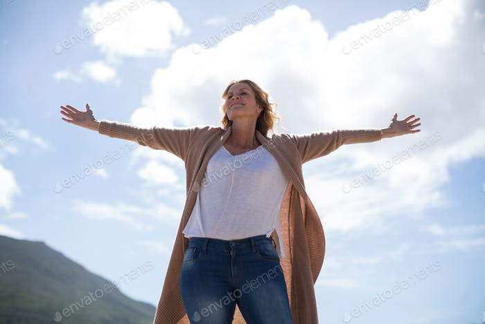 Mature woman with arms outstretched standing on the beach