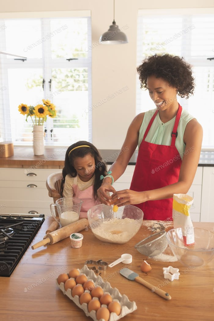 High angle view of African American mother and daughter baking cookies in kitchen at home