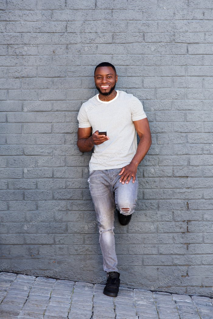 smiling man with smart phone leaning on gray wall