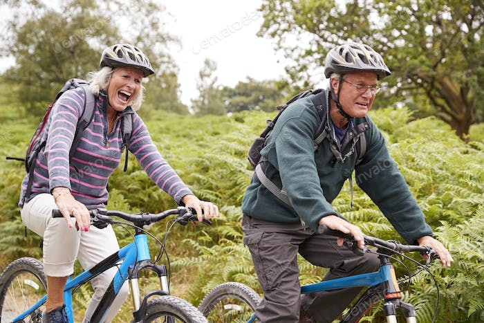 Senior couple riding mountain bikes in the countryside during a camping holiday, side view, close up