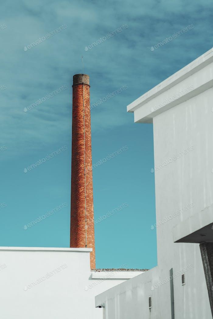Red smoke pipe behind building walls