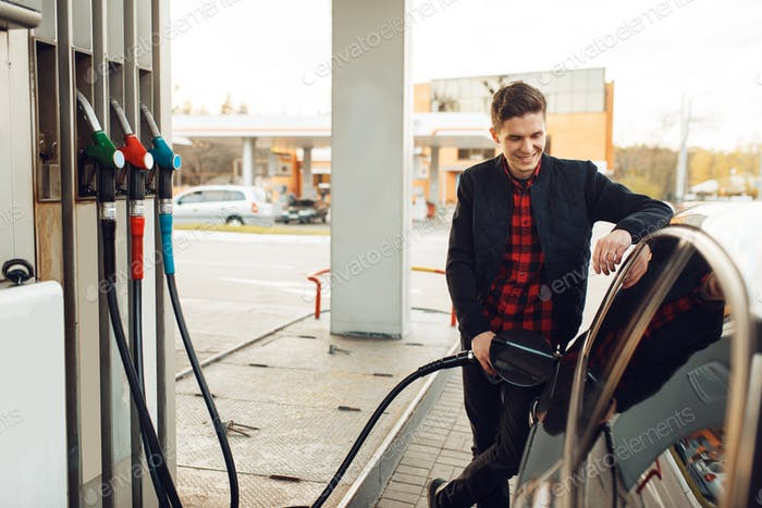 Man fuels vehicle on gas station, bottom view