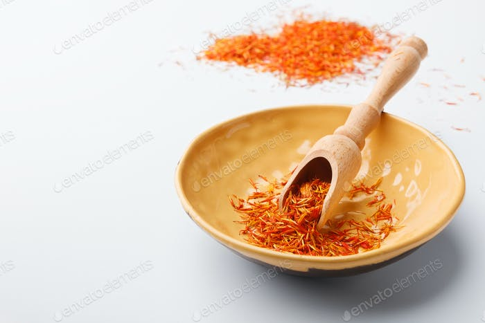 Traditional dry saffron spice in plate on white table