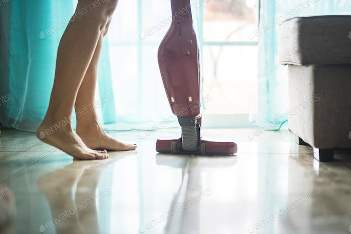 Nudism lifestyle concept for girl alone at home cleaning the floor with modern stuff