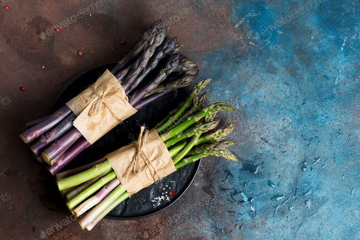 Fresh natural organic two bundles of green and purple asparagus vegetables on a dark stone