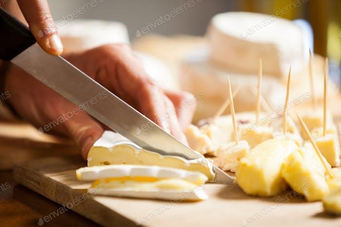 Personal de corte de queso en mostrador en el mercado