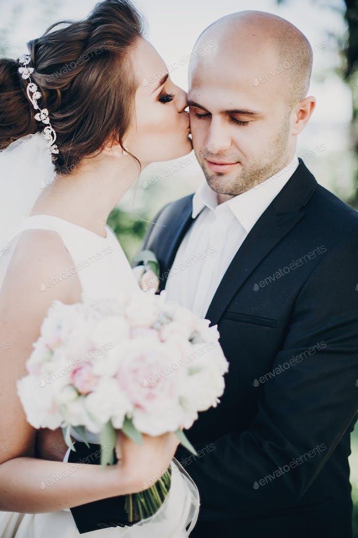 Stilvolle Braut und Bräutigam sanft küssen draußen