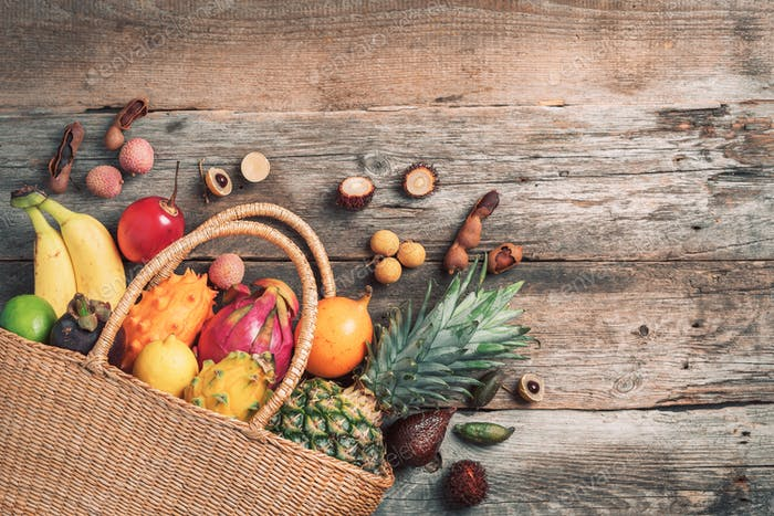Tropical fruits in a basket on wooden background. Top view. Copy space. Tropical fruits flat lay