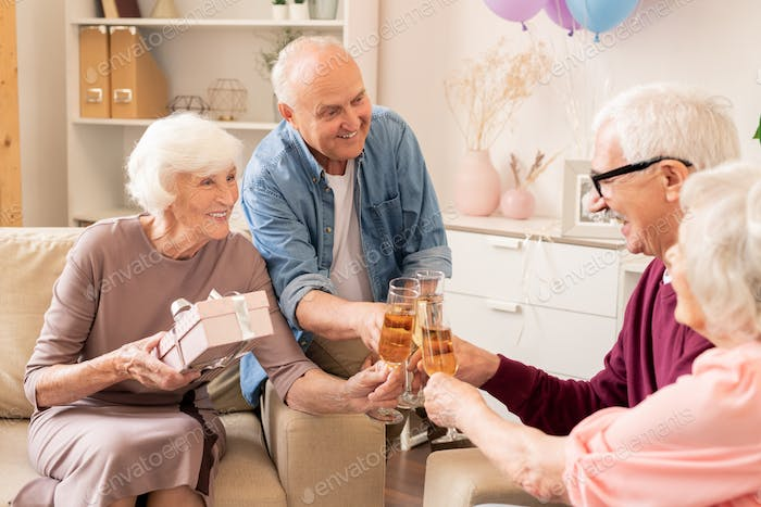 Group of cheerful senior friends with champagne making toast