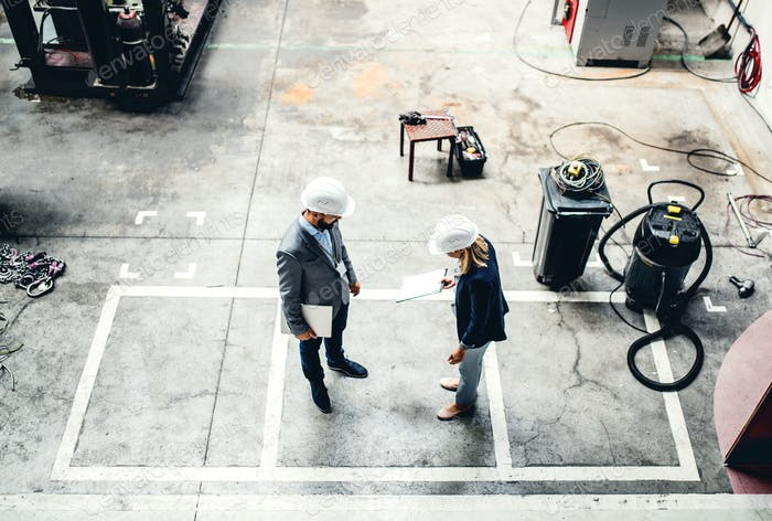 A high angle view of an industrial man and woman engineer in a factory.