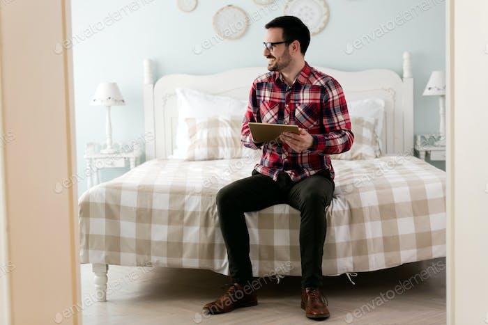 Junge gutaussehender Mann mit digitalem Tablet auf dem Bett