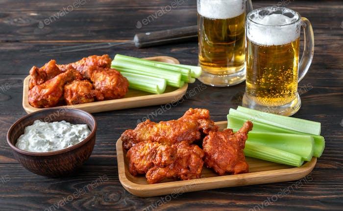 Buffalo wings with mugs of beer