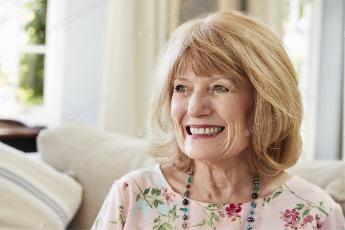 Smiling Senior Woman Sitting On Sofa At Home