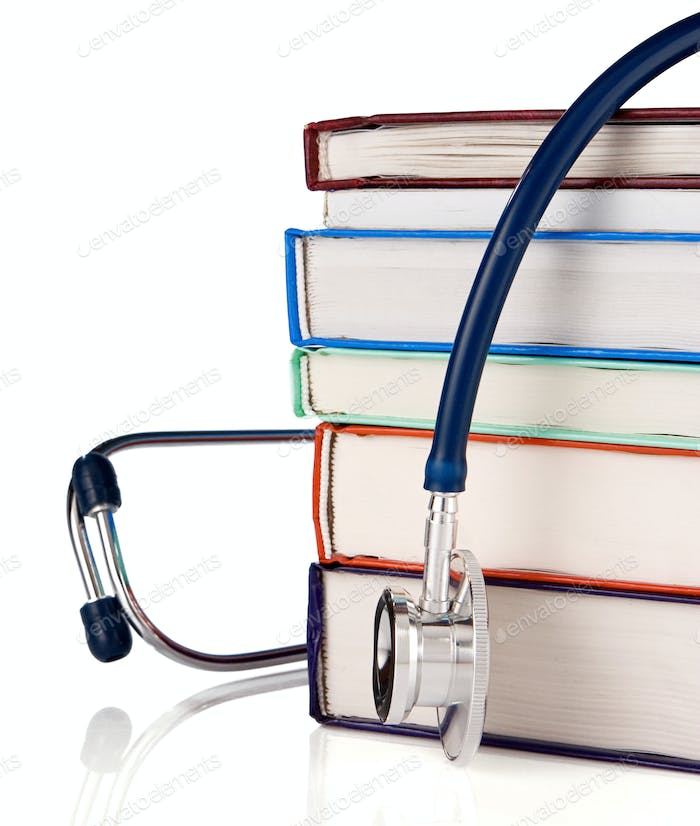 pile of old books and stethoscope isolated on white