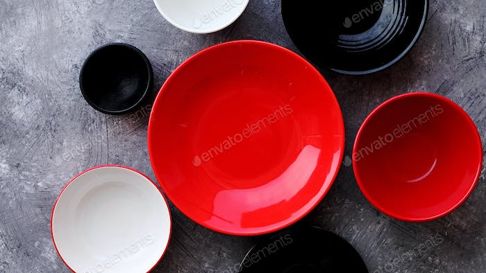 Collection of empty colorful decorative ceramic bowls on grey stone background