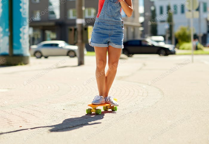 teenage girl riding skateboard on city street