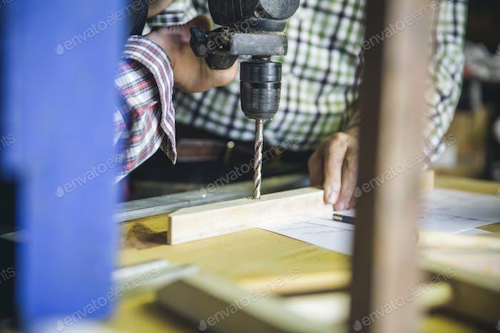 Unrecognizable couple drilling a wooden batten