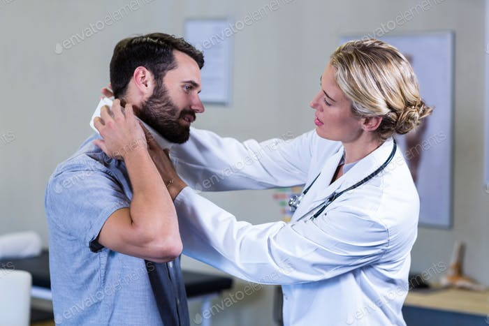 Physiotherapist examining neck of patient