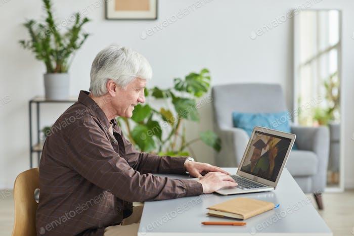 Mature father watching graduation online
