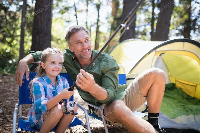 Father and daughter fishing at campsite in forest