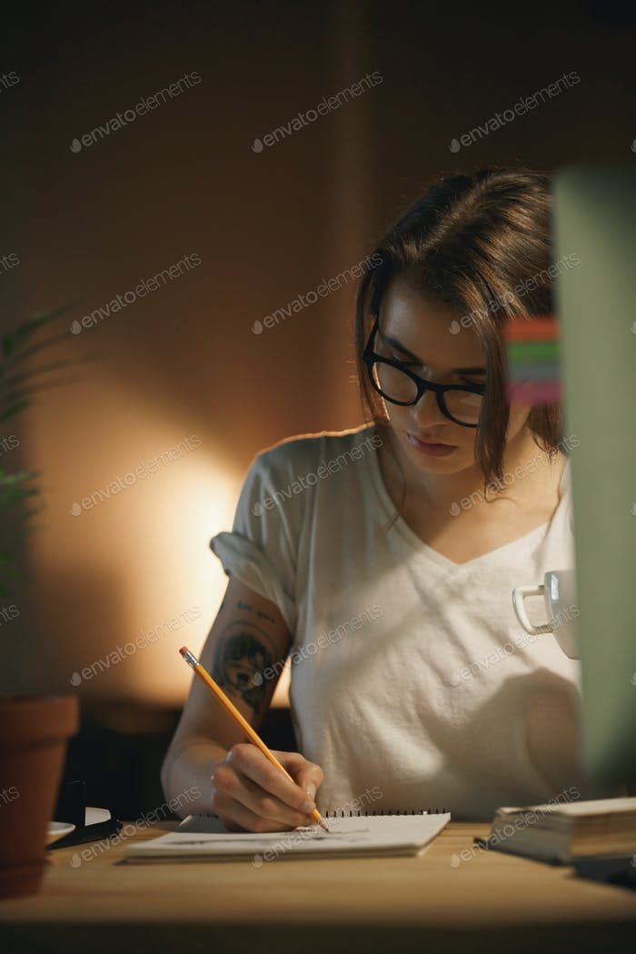 Serious young woman designer sitting indoors at night writing notes