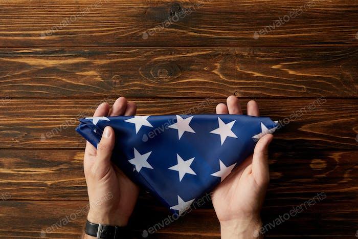 tiro recortado del hombre sosteniendo la bandera americana plegada sobre fondo de madera