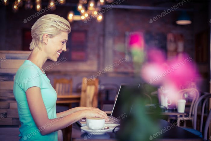 Pretty blonde using laptop computer at the cafe