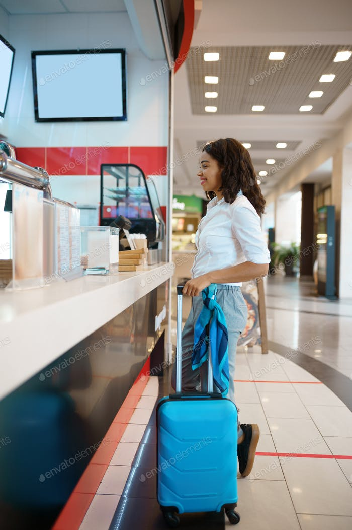 Woman with suitcase in fastfood cafe, airport