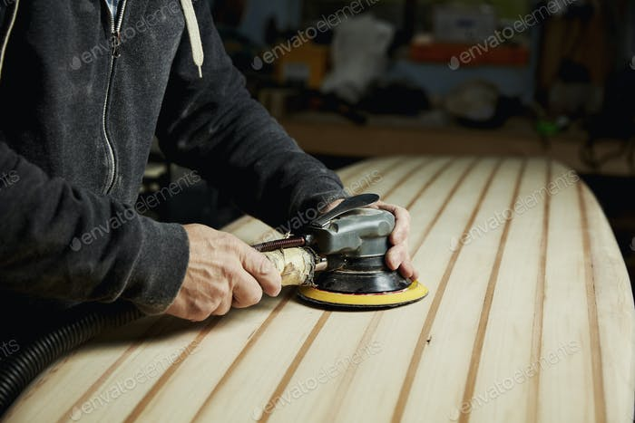 A man finishing the surface of a wooden surfboard with an electrical sander.