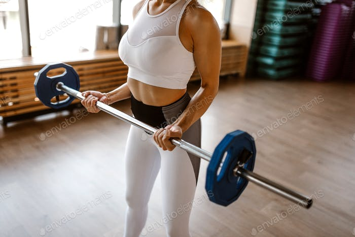 Athletic girl dressed in white sports top and tights lifts barbell in the gym