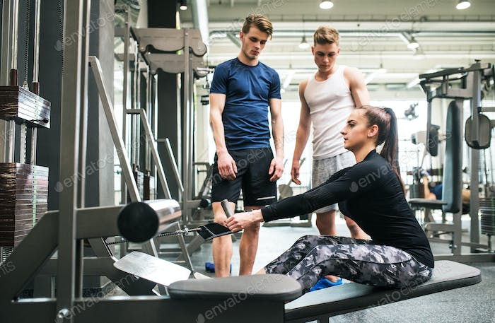 Young men in gym looking at trainer working out on cable weight machine.