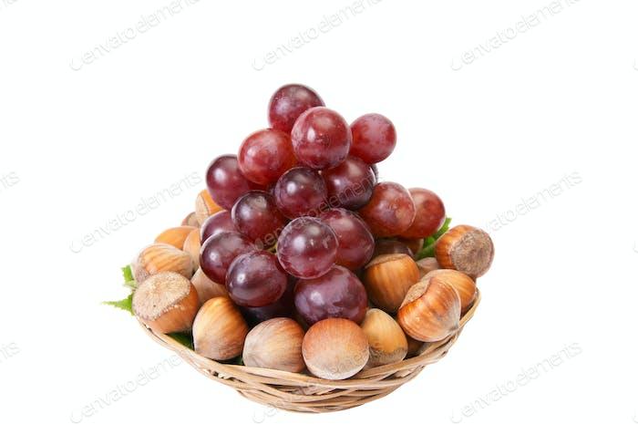 Leckere, reife Haselnüsse und Trauben isoliert auf weißem Hintergrund.