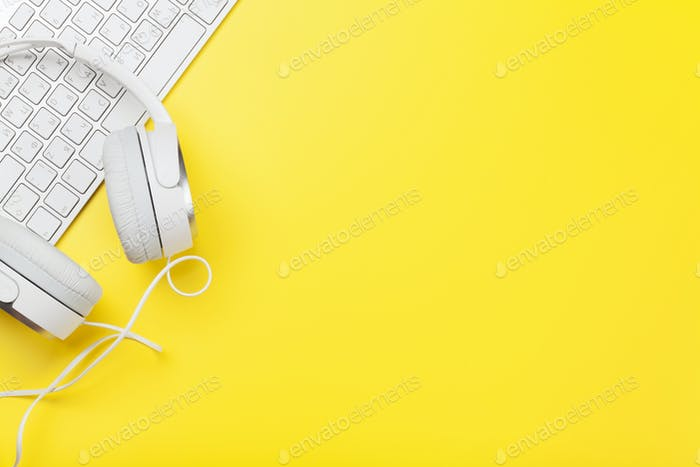 Office yellow workplace with headphones and pc