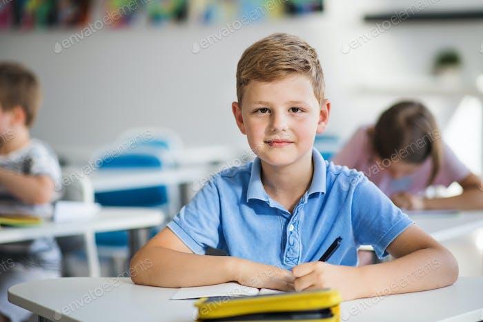 Ein kleiner Schuljunge sitzt am Schreibtisch im Klassenzimmer auf der Lektion, Blick auf die Kamera