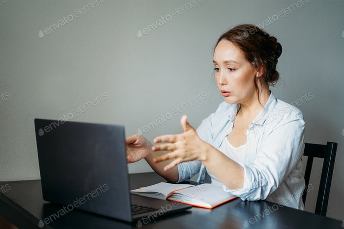 Adult woman reads terrible news by laptop