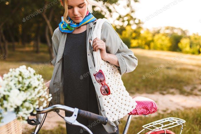Nahaufnahme Mädchen mit weißen Tasche stehend mit Fahrrad und Wildflowe