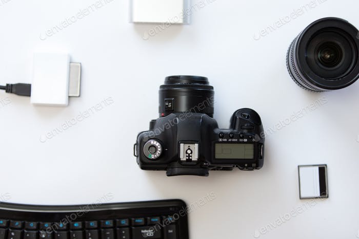 White desk with a professional camera and accessoires