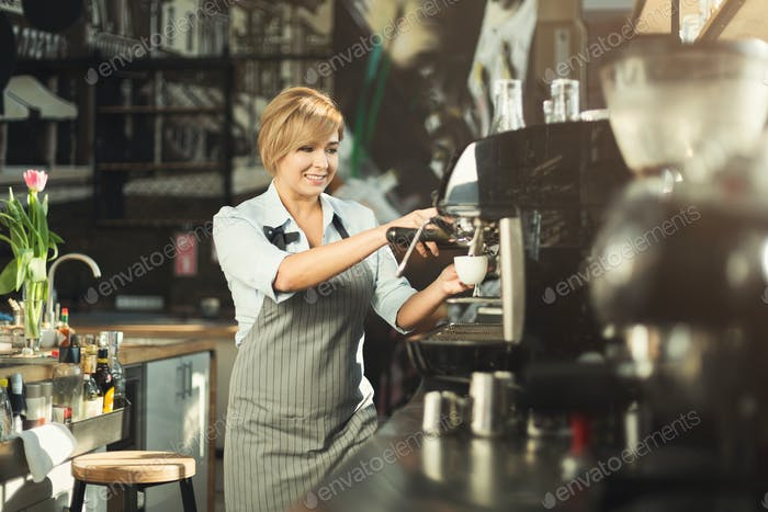Experienced barista making coffee in professional coffee machine