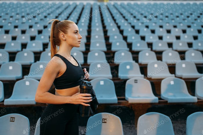 Female runner in sportswear on stadium tribune