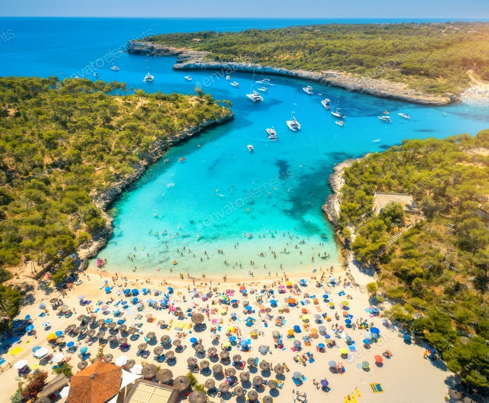 Aerial view of sandy beach with umbrellas, boats in sea bay