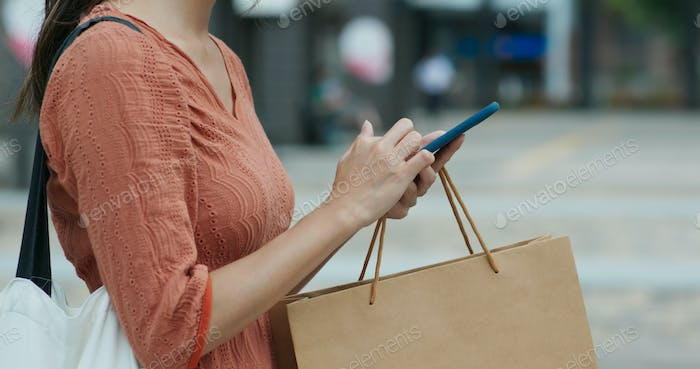 Woman use of mobile phone with shopping bag