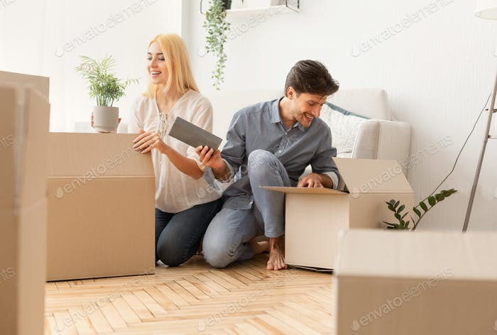 Gladful Couple Unpacking Boxes After Moving Into New Apartment