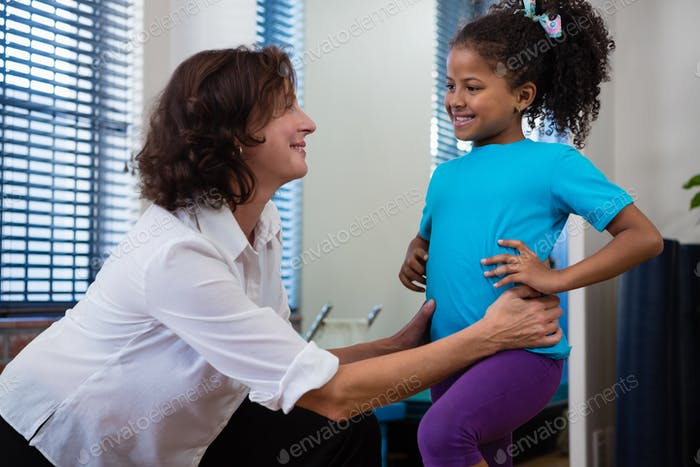 Physiotherapist giving back massage to girl patient in clinic