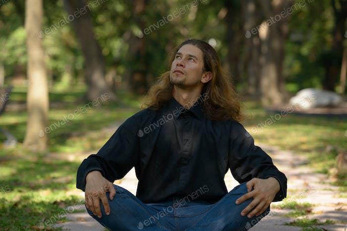 Handsome bearded businessman with long hair at the park