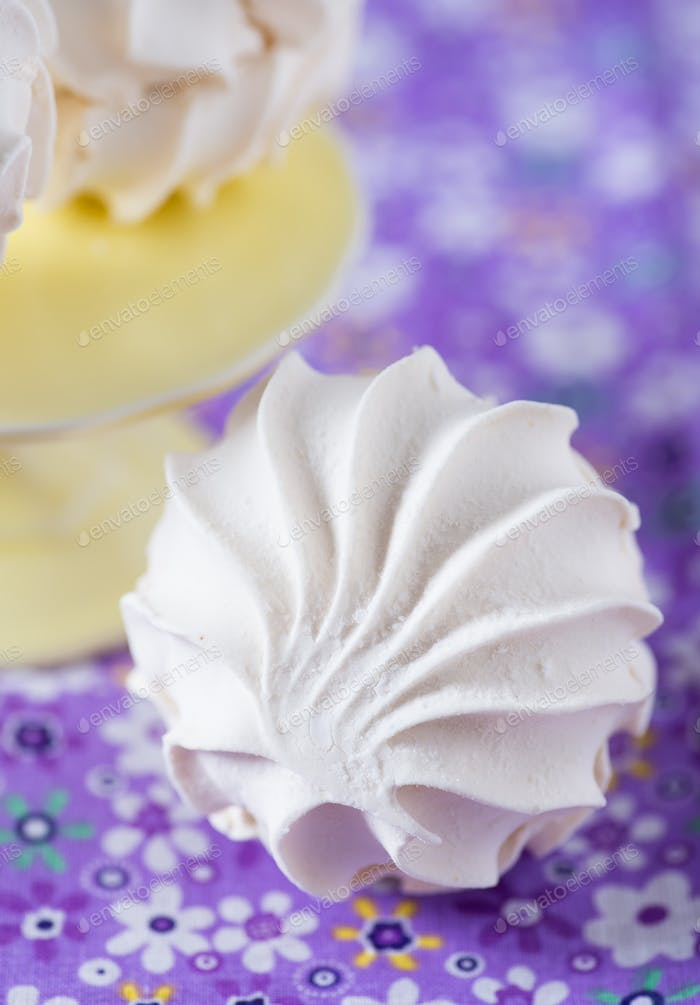 Vanilla marshmallows over purple background