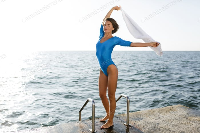 Cute woman in blue swimsuit standing and holding white towel while raising her hands up