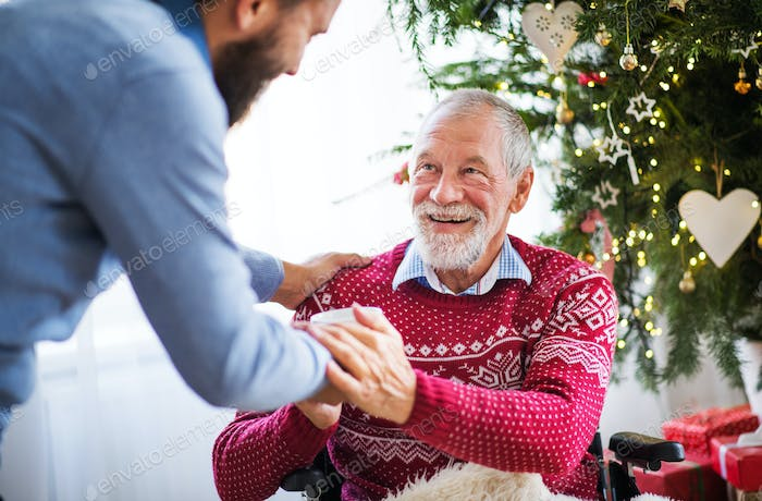 A hipster man giving drink to his senior father in wheelchair at Christmas time.