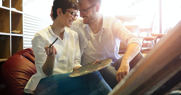 Beautiful young woman and a handsome man attending a painting workshop together
