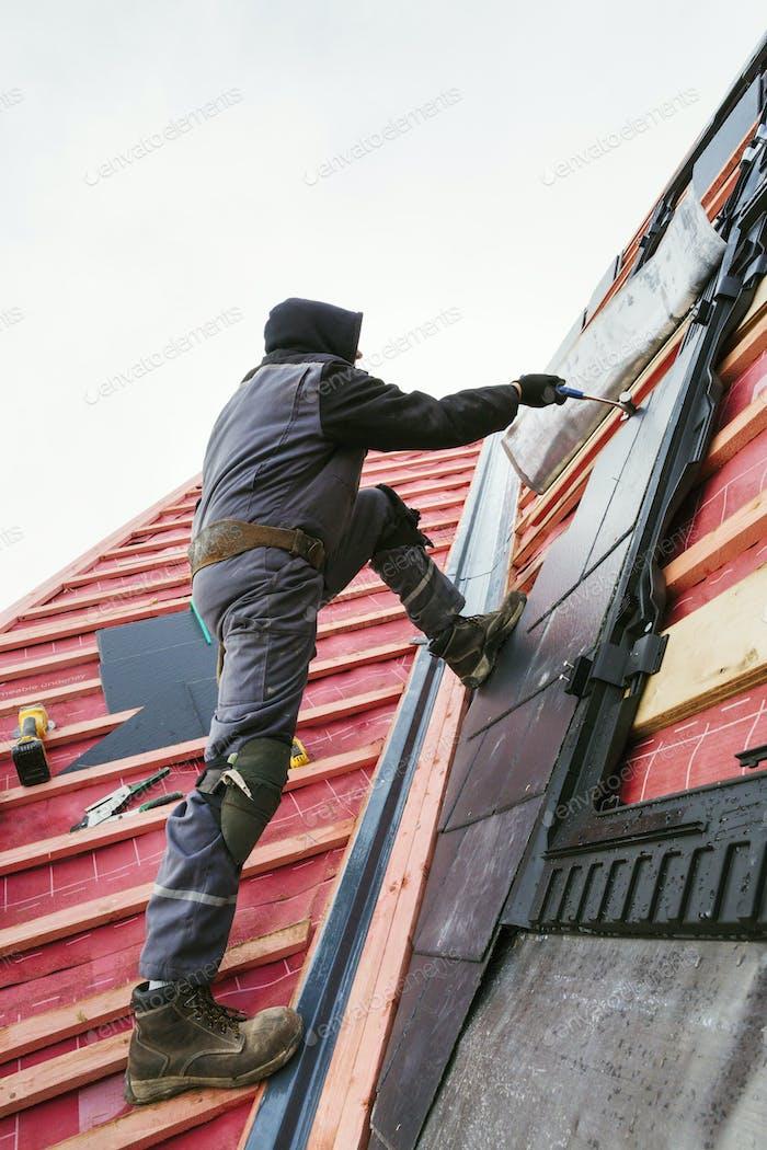Ein Dachdecker, der die Fliesen auf einem Hausdach ersetzt.
