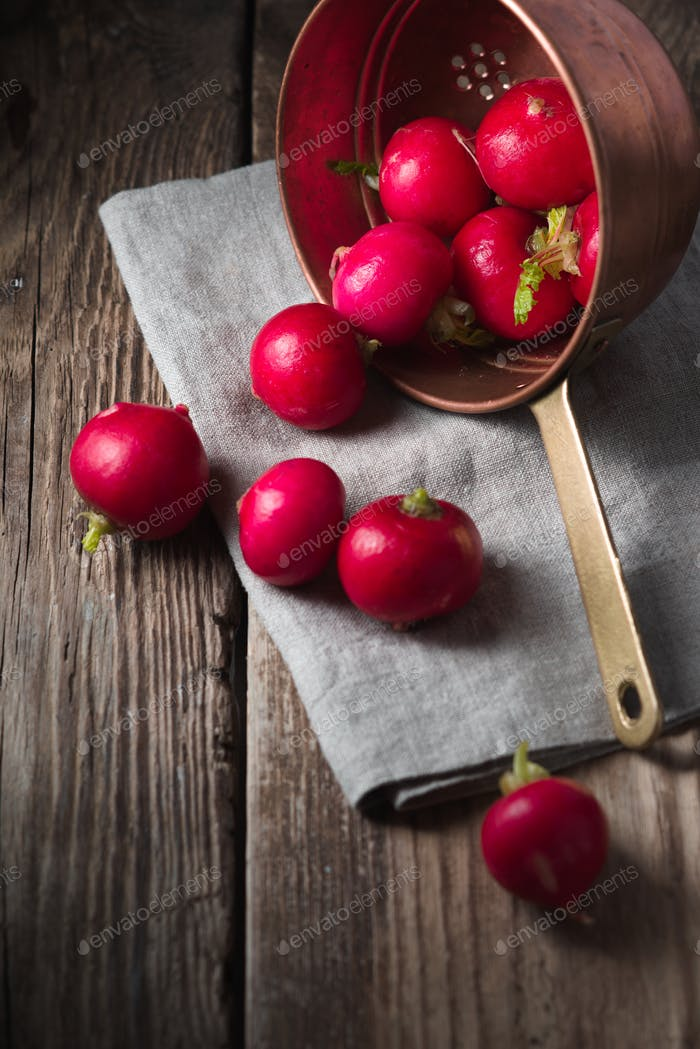 Red radishes in a colander on a wooden table